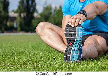 Young healthy athlete is warming up in stadium - Close up of...