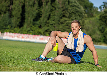 Cheerful young male runner is resting on grass - Attractive...