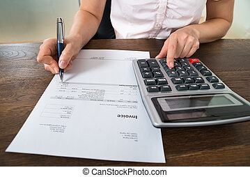 Businesswoman Calculating Tax At Desk - Close-up Of Female...