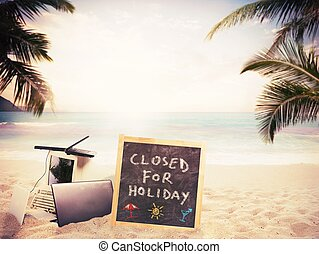 Closed for holiday - Blackboard and computer on the tropical...