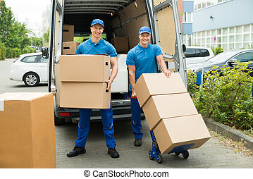Two Workers Loading Cardboard Boxes In Truck - Two Happy...