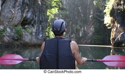 old man paddles among sunlit cliffs in tropics - old man in...