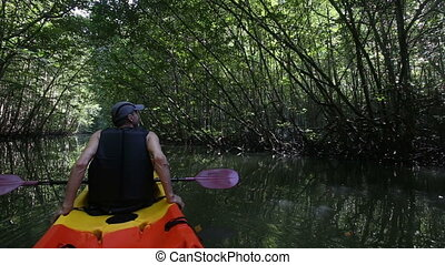 old man drifts on kayak down river among jungle - old man in...