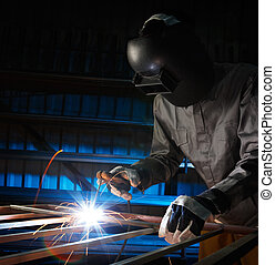 welder working - man welding in workshop with safety...