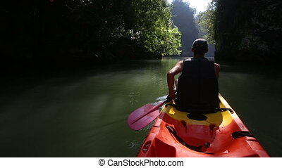 old man drifts on kayak down river along sunlit canyon - old...