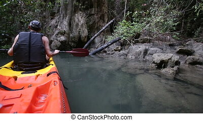 old man drifts on kayak among over-hanging branches - old...