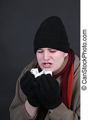 Winter flu - Teenage male sneezing into a tissue dealing...