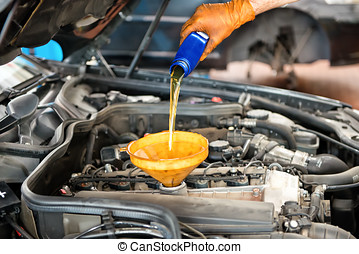 Mechanic topping up the oil in a car