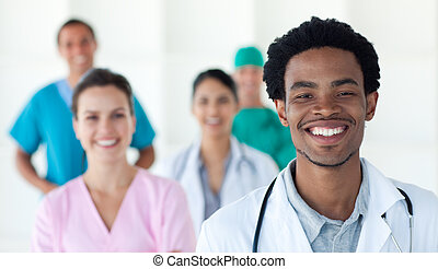 Multi-ethnic medical people smiling at the camera against a...