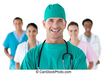 Smiling surgeon in front of his team against a white...