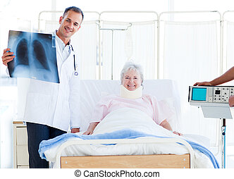 A patient with a neck brace looking at an x-ray with her doctor