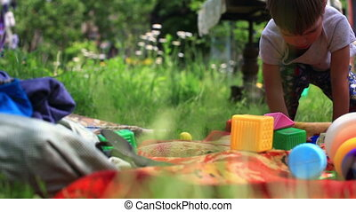 Little boy playing with toys at a garden. dolly shot