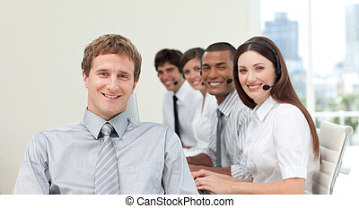 Young manager in front of his team in a call center