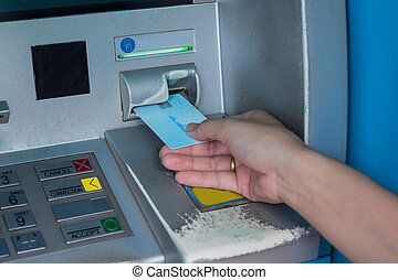 Hand inserting ATM credit card into bank machine