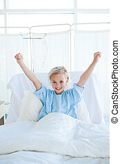Happy child patient punching the air on a hospital bed