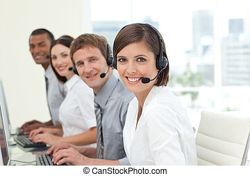 Happy co-workers with headsets on working in call center...