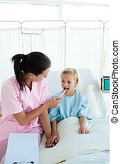 Attractive nurse examining a little female patient in a...