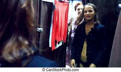 Young smiles woman trying on clothes in a clothing store In the locker room shop, shows her grandmother