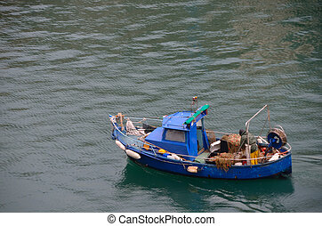 small blue boat of a fisherman in the sea