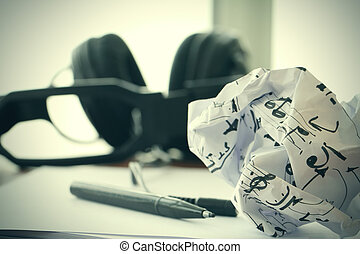 composing music concept with shallow DOF evenly matched jack of headphone and crumpled musical notes paper