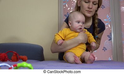 mother teach baby sit - Smiling woman mother teach her cute...