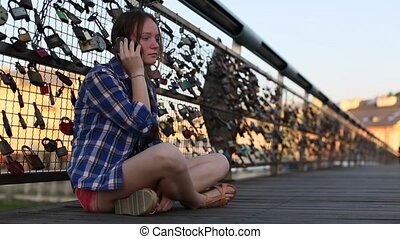 Young cute girl talking on phone sitting on a pedestrian...
