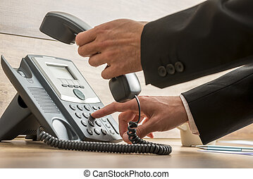 Communication operator dialing a telephone number while...