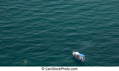Boat in the azure sea camera high - The boat is at sea...