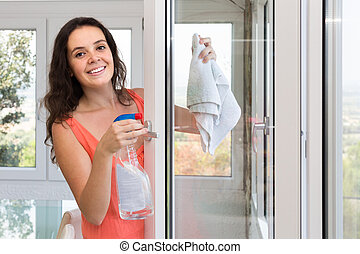 Housewife cleaning windows - Happy young housewife cleaning...