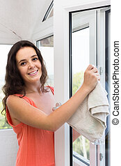 Housewife cleaning windows - Smiling housewife cleaning...