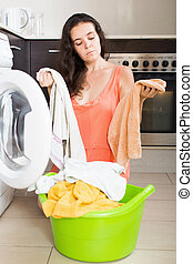 Woman tired and washing clothes in machine at home laundry