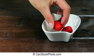 Inserting strawberries into the white bowl - White bowl is...