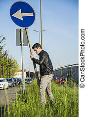 Young Man with Road Sign in Long Roadside Grass - Young Man...