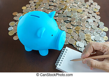 blue piggy bank and hand writing on notepad, writing income...