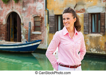Smiling woman tourist in Venice standing near canal - Ah,...