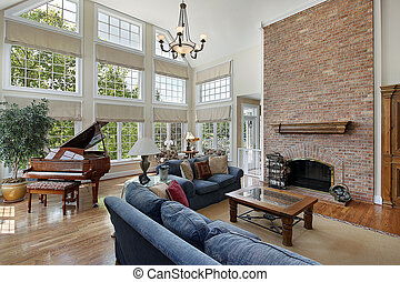 Family room with brick fireplace and two story windows