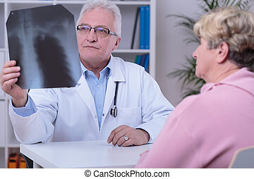 Checking the xray photo - Elderly professional physician...