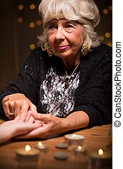 Mature female foretelling from hand - Portrait of mature...