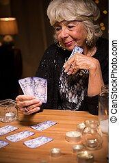 Smiling tarot reader holding cards - Image of smiling elder...