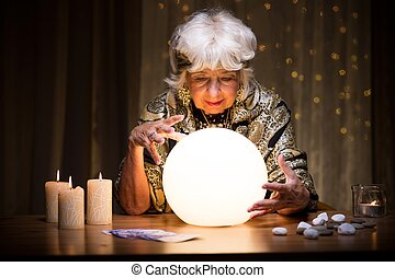 Foretelling future from crystal ball - Photo of woman...