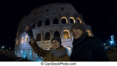 Selfie of tourists against Coliseum at night - Wide angle...