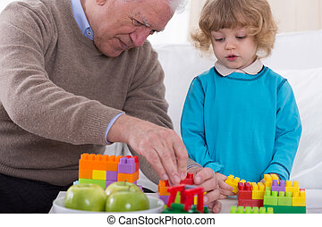 Man and grandson - Older man helping his little grandson to...