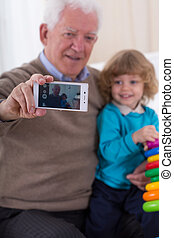Selfie with grandson - Aged smiling man doing selfie with...