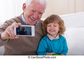 Taking photo by phone - Smiling grandfather with grandson...