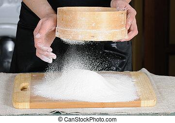 flour sieved - Flour sifting through a sieve for a baking