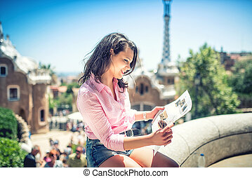 Pretty attractive girl studying map while traveling on a...