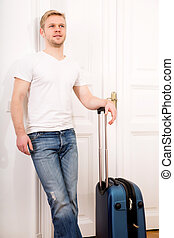 Traveller - A young man going to travel with a suitcase.