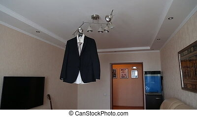 Grooms suit hanging on the door frame