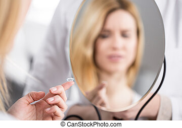 Using first time contact lenses - Young woman using first...