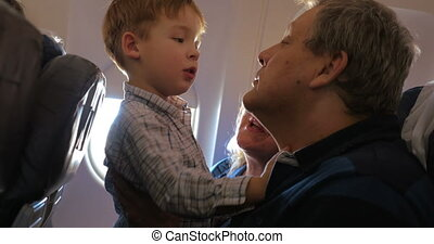 Child exploring grandfathers face in the plane -...